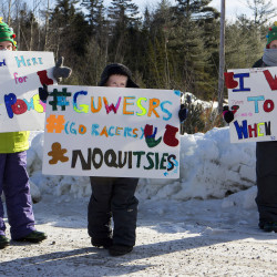Tarynn Pollman (from left), 9, James Emerson, 5, and Kennedy Emerson, 10, hold up signs cheering on runners on the Golden Road during the second Millinocket Marathon and Half Saturday. The free race drew hundreds of people to the town. Ashley L. Conti | BDN