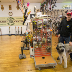 Dan Sanborn, the owner of Old Town Archery & Survival, stands in the newly renovated shop with his dog, Leo, on Nov. 29, a few days before the shop's re-opening celebration. Sanborn purchased the shop Oct. 1 and has since remodeled the shop, adding survival and camping gear to the facility's retail space. The shop's old sign is displayed behind him, by one of the shop's indoor shoot ranges.