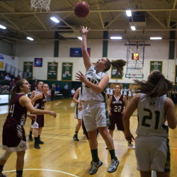 Husson University's Chandler Guerrette (center) goes up for two past University of Maine at Farmington's Kelly Pomerleau (right) during their basketball game at Newman Gymnasium in Bangor, Dec. 1, 2015.