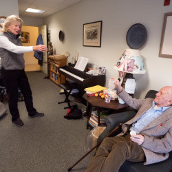 Hal Owen, 92, toasts Sally Davis with a glass of water before taking his morning medication at the Camden Hills Villa senior living facility Wednesday. Davis, a caregiver, visits Owen twice daily and helps him with his medication and other minor chores.