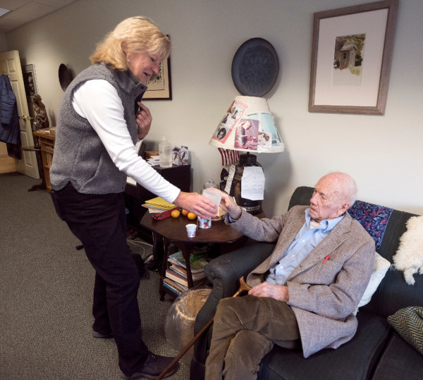 Caregiver Sally Davis hands a glass of water to Hal Owen, 92, so he can take his morning medication at the Camden Hills Villa senior living facility Wednesday. Davis visits Owen twice daily and helps him with his medication and other minor chores.