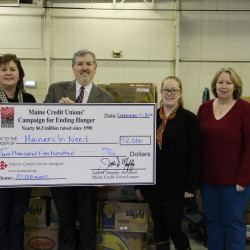 (L-R) Jon Paradise (second from left), Vice President of Governmental Affairs at the Maine CU League, presents a check to Melissa Huston of the Good Shepherd Food Bank that will help purchase 10,000 holiday meals for Maine families.  Looking on are representatives from several of the food pantries that will benefit from the contribution.
