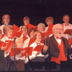 Conductor Daniel Ladner and members of the Caribou Choral Society, including 40-year members Donna Small (back row, third from right) and Mary Lou Nelson (next row down, next to Small), perform in this undated photo.