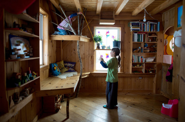 Jonah Palumbo, 9, (right) and his brother Ara, 4, play with a toy fairy hanging from the ceiling of the living area. Because the family of five lives in a 432-square-foot house, they opted to not have furniture. Instead, John built in a &quotcouch&quot along the wall and a small play loft above it.
