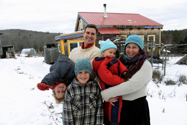 John Palumbo, his wife Nyla Bravesnow and their three sons Jonah, 9, Ara, 4, and Kai, 2, at their home in Thorndike. John and Nyla gave up their hectic 9-to-5 schedule about a decade ago in exchange for a simpler lifestyle in Thorndike. The couple and their three young sons live in a 432-square-foot home on their 8-acre farm called Many Hands Farm.