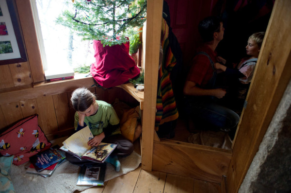Jonah Palumbo, 9, reads a book in a small reading area as his father, John, helps Ara, 4, get into his snow gear.