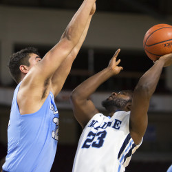University of Maine's Jaquan McKennon (right) goes up for two past Columbia's Chris McComber during their basketball game at the Cross Insurance Center in Bangor on Monday.