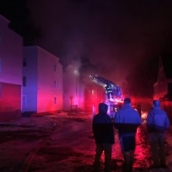 Three men watch firefighters battle a Munjoy Hill apartment building fire Monday night. Nearly a dozen people are left without a home after the fire broke out at the Cumberland Street apartment building.