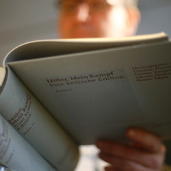 "The owner of a book shop looks through a copy of the book ""Hitler, Mein Kampf."""