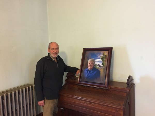 Brother Arnold Hadd of the Sabbathday Lake Shaker Community in New Gloucester stands in the meeting room with a portrait of Sister Frances Carr on Tuesday. Carr died Monday at the age of 89.