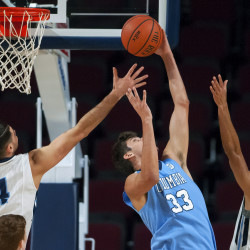Columbia's Luke Petrasek (center) leaps for a rebound against the University of Maine's Marko Pirovic (left) and Austin Howard during their basketball game at the Cross Insurance Center in Bangor on Monday.
