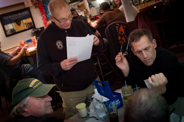 Paul Steinhagen (left) and Michael Clenott (right) listen as Howie Chadbourne repeats trivia questions on Tuesday night at Howie's Pub on Washington Avenue in Portland. Chadbourne is selling his pub and getting out of the business after tending local bars for more than 40 years.