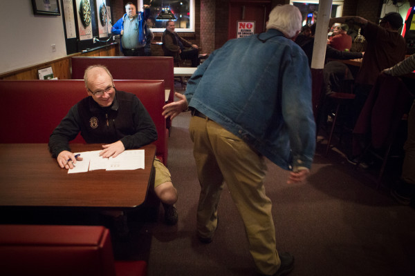 Howie Chadbourne (left) jokes with a familiar patron while deciding the winner of the weekly trivia contest on Tuesday night at Howie's Pub on Washington Avenue in Portland. Chadbourne is selling his pub and getting out of the business after tending local bars for more than 40 years.