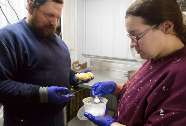 Andrea Rollins (right) adds a bit of salt to fresh butter so Ernest Rollins can mix it in on Friday at Rollins Orchard in Garland. Rollins Orchard began making butter in 2015.