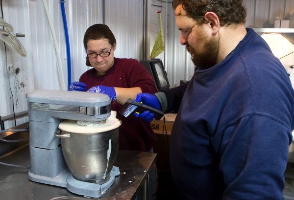 Ernest Rollins (right) checks the temperature of cream while Andrea Rollins keeps the top on the mixer while making butter on Friday at Rollins Orchard in Garland. Rollins Orchard began making butter in 2015.