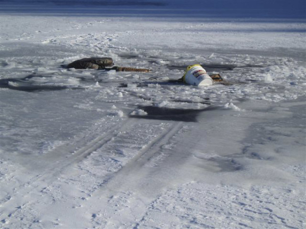 Items belonging to three ice fisherman lay on top of thin ice on Long Lake in northern Maine in January 2011. The men went through the ice on an ATV and tote sled. All got out safely.