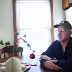 "Tom Picard sits in his home in Millinocket Saturday. Picard says he lives ""the new normal."" As a millworker, Tom has been laid off 10 times since 1980. For the last few years he has been making the weekly commute to his new job 130 miles away, at the Huhtamaki plant in Waterville. This past summer, he divorced his wife, Tammy Shorey Picard, as the commuting was putting a strain on their relationship."