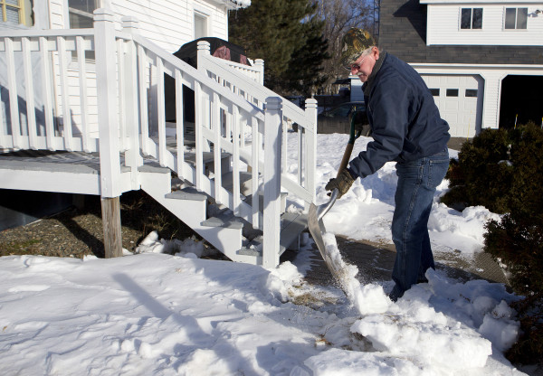 Tom Picard shovels a path to his gas line at his home in Millinocket Saturday. Picard says he lives &quotthe new normal.&quot As a millworker, Tom has been laid off 10 times since 1980. For the last few years he has been making the weekly commute to his new job 130 miles away, at the Huhtamaki plant in Waterville. This past summer, he divorced his wife, Tammy Shorey Picard, as the commuting was putting a strain on their relationship.