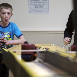 Ethan Riley (left), 9, pulls the lever on his belt sander while racing Vicktoria Brayman, 15, during the Penobscot County chapter of the United Bikers of Maine annual fundraising belt sander racing series at City Side Restaurant in Brewer on Saturday.