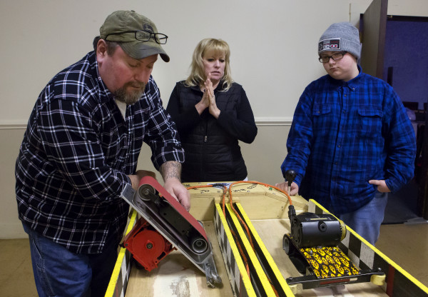 Kenny Rogerson (left) makes final adjustments to his wife's, Karen Rogerson, belt sander before her race against John Rogerson II, 15, during the Penobscot County chapter of the United Bikers of Maine annual fundraising belt sander racing series at City Side Restaurant in Brewer on Saturday.