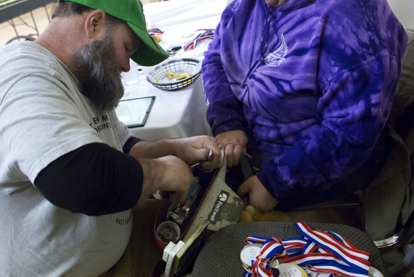 Dale Holmes (left) adjusts his belt sander before another heat at the Penobscot County chapter of the United Bikers of Maine annual fundraising belt sander racing series at City Side Restaurant in Brewer on Saturday.