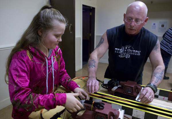 Paige Hanson (left), 12, and John Powers set up their belt sanders during the Penobscot County chapter of the United Bikers of Maine annual fundraising belt sander racing series at City Side Restaurant in Brewer on Saturday.