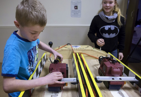 Ethan Riley (left), 9, sets up his belt sander to race Vicktoria Brayman, 15, during the Penobscot County chapter of the United Bikers of Maine annual fundraising belt sander racing series at City Side Restaurant in Brewer on Saturday.