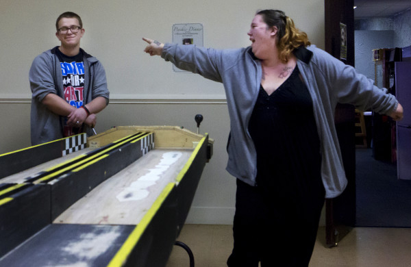 Heather Brayman-Mitchell (right) points and laughs after beating Caleb Soucier, 16, in their heat during the Penobscot County chapter of the United Bikers of Maine annual fundraising belt sander racing series at City Side Restaurant in Brewer on Saturday.