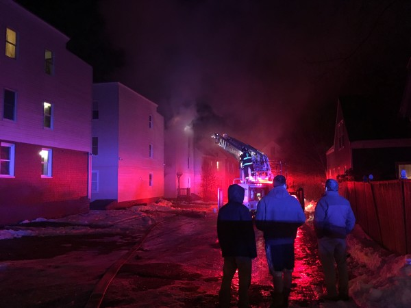 Three men watch firefighters battle a Munjoy Hill apartment building fire Jan. 2 in Portland.