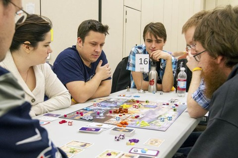 Jillian Piehler (from left), Keith Piehler and Joey Leask play the board game Euphoria with others during a SnowCon Gaming Convention.