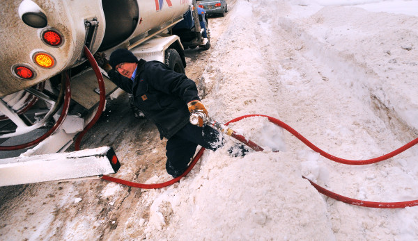 Greg Hamilton, a delivery driver with Dead River Co., struggles through a waist-high snowbank after filling the oil tank at a Brewer home in this December 2013 file photo.