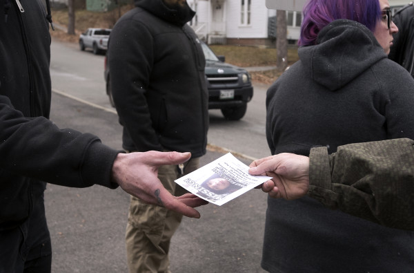 A flier is handed out while people search Sanford Street and other nearby streets on Dec. 5, 2016, for Paul Francis III, who has been missing since Dec. 2.
