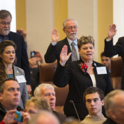 Maine senators raise their right hands as they are sworn in during the first session of the 128th Legislature at the State House in Augusta in this December 2016 file photo.