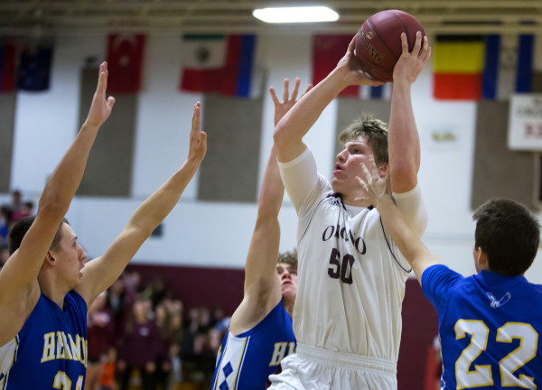 Orono's Keenan Collett (center) puts up a shot past Hermon's Jordan Bishop (left) and Cody Hawes during their basketball game in Orono Wednesday.