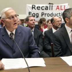 "Protesters hold a banner as Austin DeCoster (left), owner of Wright County Egg, and his son Peter DeCoster testify before the House Oversight and Investigations Subcommittee hearing on the ""Outbreak of Salmonella in Eggs"" on Capitol Hill in Washington on Sept. 22, 2010."