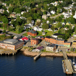 A Kansas City developer has agreed to partner in the renovation of a former 28,800-square-foot sardine can manufacturing plant in downtown Eastport, pictured partially on a pier overhanging the water. The owners of the building hope to complete the $18 million project by the summer of 2018.
