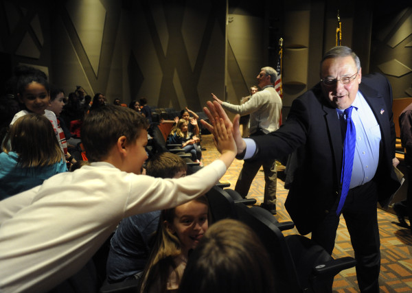 Gov. Paul LePage high-fives third-grader Tyler Alexander as he exits the performing arts center after signing LD 1609 into law at the Brewer Community School, April 4, 2016.