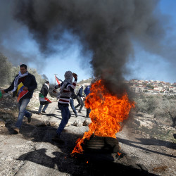 Palestinian protesters run as others hurl stones toward Israeli soldiers during clashes on Dec. 30, 2016, after a protest against the nearby Jewish settlement of Qadomem in the West Bank village of Kofr Qadom near Nablus.