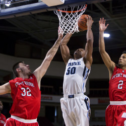 University of Maine's Vincent Eze (center) goes up strong for two past Stony Brook's Jakub Petras (left) and Michael Almonacy during their basketball game at the Cross Insurance Center in Bangor Saturday.