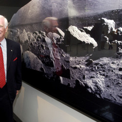 Former astronaut Gene Cernan, the last man to walk on the moon, stands next to a wall of photographs he made on the Apollo 17 mission, at the Museum of Natural History in New York, May 7, 2004.