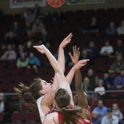 The University of Maine's Fanny Wadling (left) goes up for a shot over Hartford's Alyssa Reaves (right) and Kelly Douglass during the game at the Cross Insurance Center in Bangor Monday.