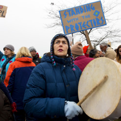 Maryanne Mattson (center) plays a drum during a peaceful protest on Bangor Mall Boulevard in November. In light of the recent violence against the peaceful water protectors at Standing Rock, Maine tribes and their allies held a flash mob round dance. For a few minutes a group of over 100 people blocked traffic at the intersection near Toys R Us to pray, sing and dance.