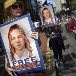 People hold signs calling for the release of imprisoned Wikileaks whistleblower Chelsea Manning while marching in a gay pride parade in San Francisco, California, recently.