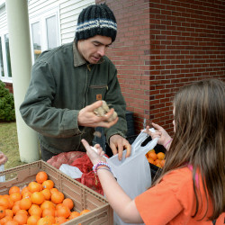 Farmer Michael Hayden of Folklore Farm in Cherryfield helps students pick vegetables to take home on Thursday at his pop-up farm stand at Milbridge Elementary School in Milbridge.