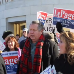People hold signs at a rally in support of Gov. Paul LePage outside the State House in Augusta in this January 2016 file photo.