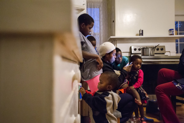 Safi Paulo (center) is surrounded by her children shortly after returning home to Thomaston from work, checking Facebook on her smartphone while chatting with her sister-in-law Yalla Kaluta (not shown) and relaxing in the kitchen.