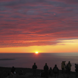 People gather a few minutes before 7 a.m. Saturday, Oct. 22, 2011, at the summit of Cadillac Mountain in Acadia National Park to see the sunrise.