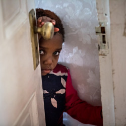 Josephine Jordan, 3, peers out from the doorway leading to her family's front hall after coming down from the upstairs to investigate the sound of visitors.