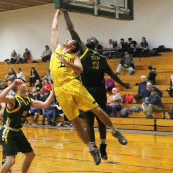 Joe McCloskey (center) of the University of Maine at Fort Kent goes up for a shot during a Jan. 12 game against SUNY Delhi. The Howland native is the only Mainer on the roster for the Bengals, who feature numerous players from California and other countries on a ballclub seeking a USCAA Division I national championship.
