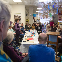 "People listen as Mary Ellen Quinn, co-coordinator of Pax Christi Maine, speaks during a ""People's Inauguration"" on Friday at the Peace & Justice Center of Eastern Maine in Bangor."